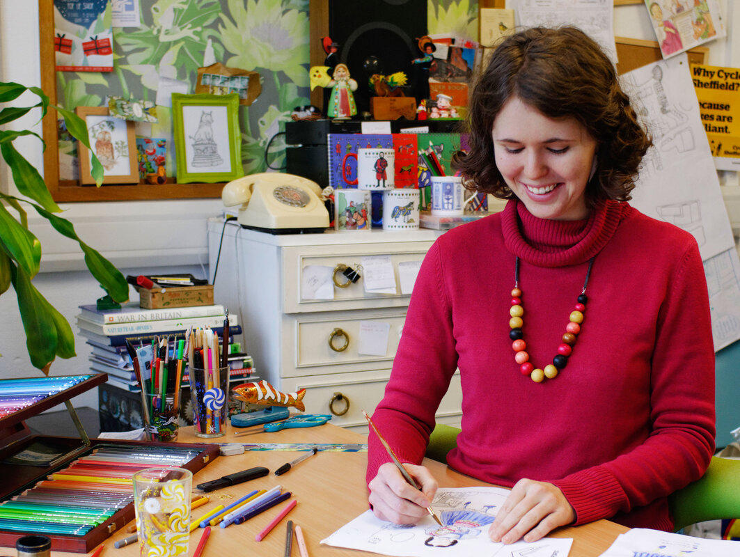 Photograph of children's illustrator and trail designer Emma Metcalfe drawing by hand in Nottingham